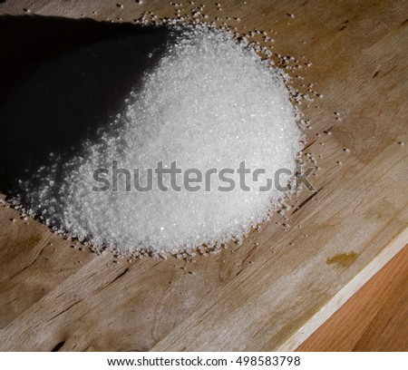 White sugar pile on wooden board