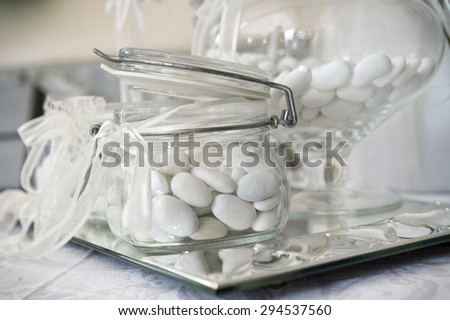 white sugared almond in glass jars on silver tray