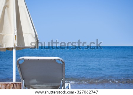 White sunbed and white closed parasol in front of blue sky and sea horizon.