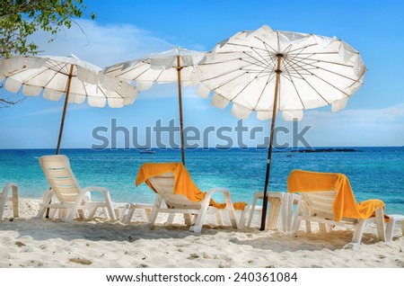White sunbeds and orange towels on sandy beach, Phuket, Thailand