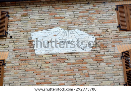 White sundial on a house wall - stock photo