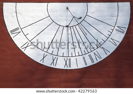 White sundial on a red wall of a monastery - stock photo