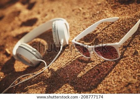 White sunglasses and headphones on sand - stock photo