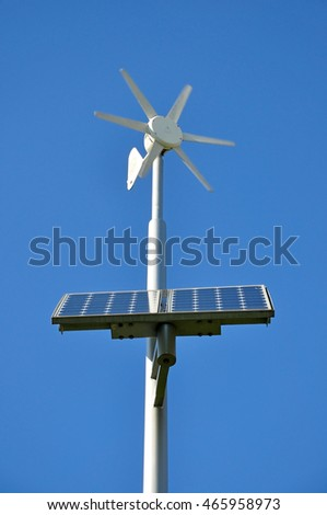 White support with moving small wind turbine and installed solar panels on a blue sky background.