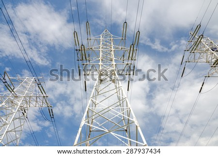 white supports of high-voltage power lines against the blue sky - stock photo