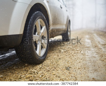 White SUV car on an offroad trail in a foggy day - stock photo