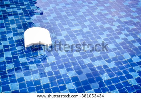 White swim board and background of rippled water in swimming pool  - stock photo