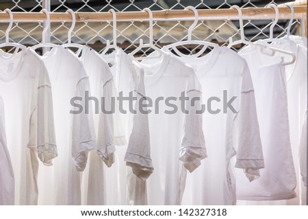 White T-shirt hangers in row - stock photo