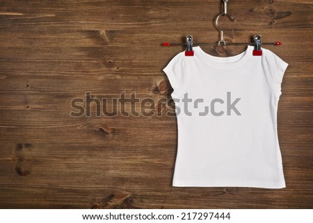 White T-shirt hanging on wooden background - stock photo