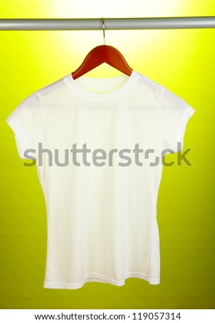 White t-shirt on hanger on yellow background