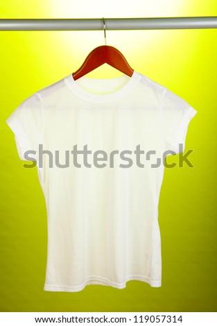 White t-shirt on hanger on yellow background - stock photo