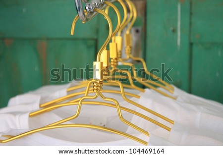 white t shirts on cloth hangers in row - stock photo