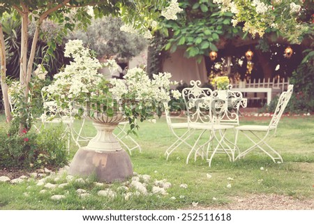 White table and chairs in beautiful garden. Vintage style pictures.