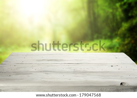white table and green and yellow sunset  - stock photo