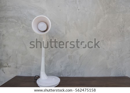 White Table lamp isolated on wooden table wall gray background .