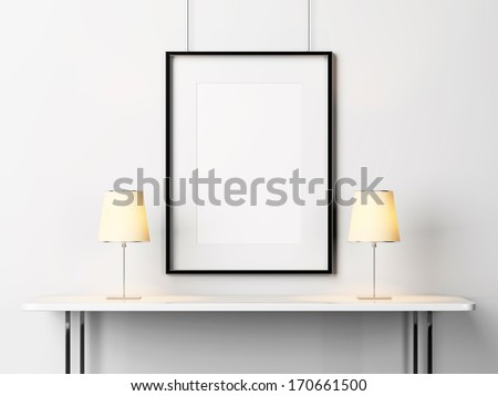 White table with lamps and blank picture frame - stock photo