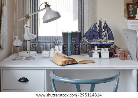 white table with wooden chair books and lamp in modern working area at home - stock photo