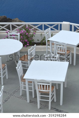 White Tables and Chairs in Greek Taverna with Ocean View - stock photo