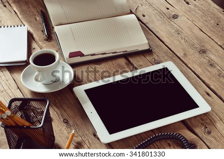 White tablet computer with on office wooden table. Copy space. Free space for text. Office workplace