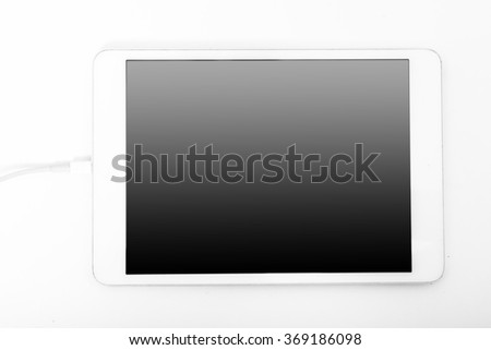 White tablet laying on the white background.