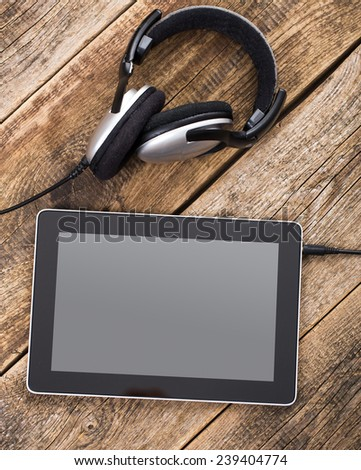 White tablet PC and headphones on the wood bench - stock photo