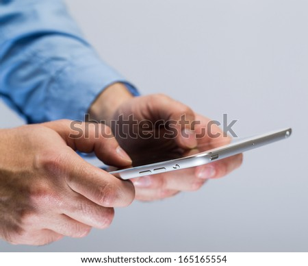 White tablet pc in hands over gray background