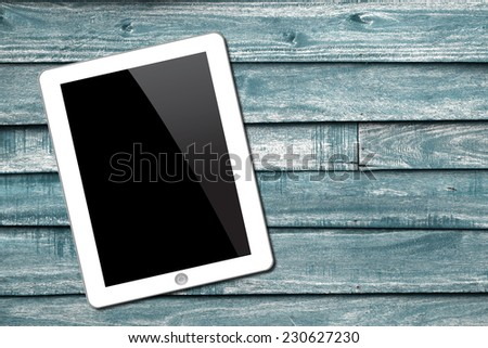 White Tablet pc on wooden background - stock photo