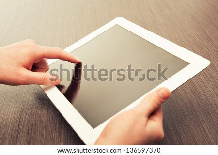 white tablet with a  blank screen in the hands