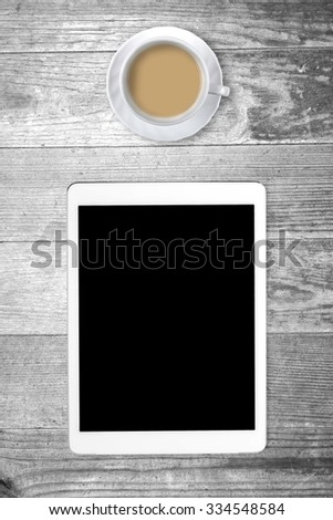 White tablet with a coffee cup on old wooden table. Blank screen with space for copy. Concept the coffee break with the use of the tablet. Vertical composition. - stock photo