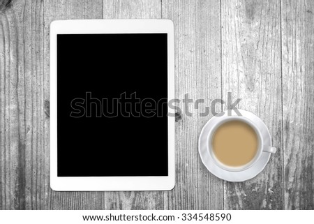 White tablet with a coffee cup on old wooden table. Blank screen with space for copy. Concept the coffee break with the use of the tablet. - stock photo