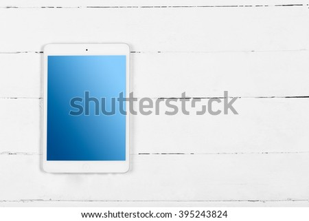 White tablet with blue screen on wooden white table - stock photo