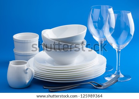 white tableware over blue background - stock photo