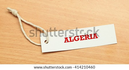 White tag on wooden background with word algeria