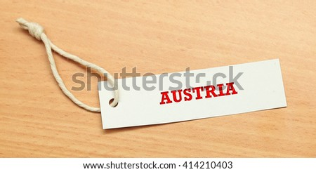 White tag on wooden background with word austria