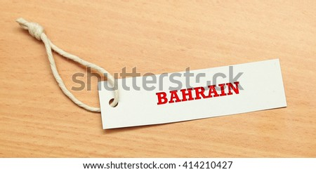 White tag on wooden background with word bahrain