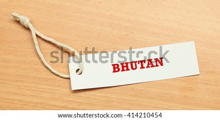 White tag on wooden background with word Bhutan