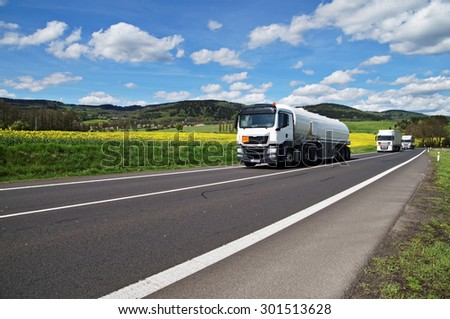 White tanker and trucks driving along the asphalt road around the yellow flowering rapeseed field in countryside. Wooded mountains in the background. Blue sky with white clouds. - stock photo