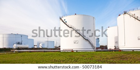 white tanks for petrol and oil in tank farm with blue sky - stock photo