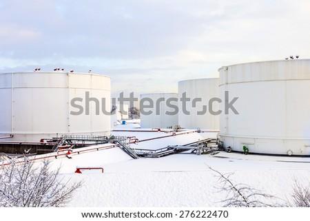 white tanks in tank farm with iron staircase in snow - stock photo