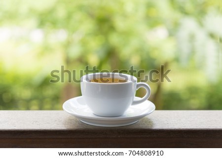 White tea cup on wooden table on green background