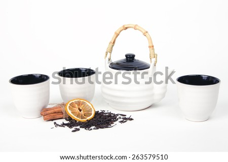 White tea set of three cups and teapot on a white background with tea, cinnamon and lemon - stock photo