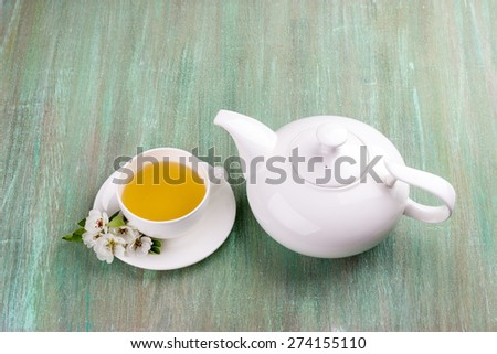white tea, white cup, saucer white, apple blossom, cherry blossom, mint, on turquoise background - stock photo