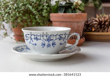 white teacup with delicate blue pattern on a table / tea cup / mug