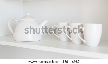 white teapot and cups on the shelf