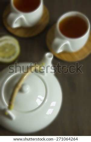 White teapot and two teacups with tea and lemon on straw plate. Shallow DOF, Blur, Toning - stock photo