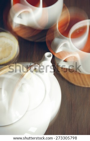 White teapot and two teacups with tea in sepia. Shallow DOF, Collage, Double Exposure effect. - stock photo