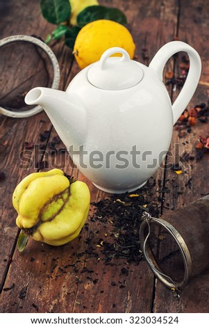 White teapot on  background of quince fruit and spilled tea - stock photo