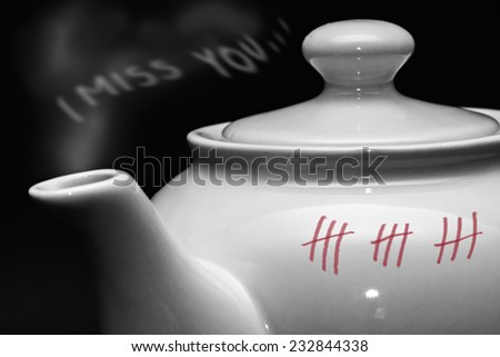 white teapot on black background - I miss you, lost and waiting, love concept - stock photo