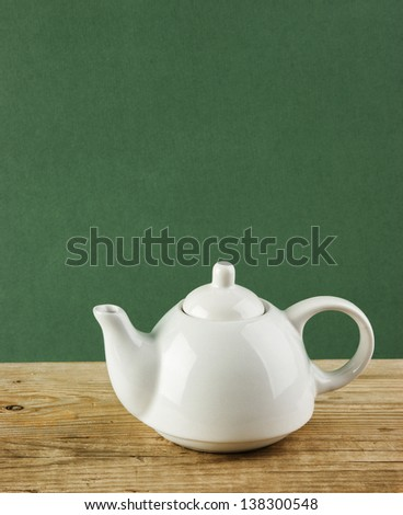 White teapot on old wooden table over green background