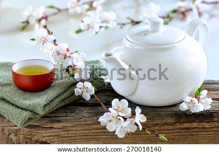 White teapot with freshly brewed green spa tea on wooden surface with a cup of healthy calming and detox tea decorated with spring blooming branches - stock photo